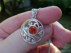 Beautiful Padparadscha Orange Sapphire Pendant. This Lab-created gemstone measures 2.50ctw and is a 8mm Round. Stone is set in .925 Sterling Silver, w/anti-tarnish protection and has beautiful scroll work around the stone. Box chain measures 18 inches. Sold (1/14/13)