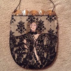 Evening Bag!  Reduced! This is a hand painted and lace overlay vintage evening bag. The lace on the top and right side are separated,but can be repaired or covered with beading in spots. This bag has long cord to wear on shoulder- it hangs 16 inches and can be tied shorter easily. The inside is black velvet in perfect condition. Sold As Is I would put some sequined appliqués in areas where lace is frayed to  cover the areas and keep with the antique look Bags