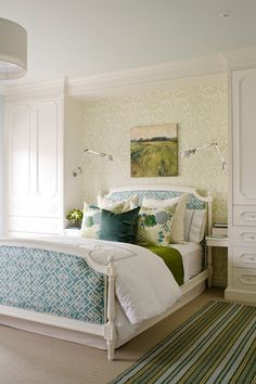 This sweet-yet-sophisticated design includes white furniture, wallpaper and a lively bedding set.    A new palette of soft, silvery greens and blues create a muted backdrop for vibrant patterned fabrics in teal, white and grass green. The existing bed frame was freshened up with bright white paint and upholstered in a bold geometric print.