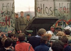 West Berliners crowd in front of the Berlin Wall early on November 11, 1989 as they watch East German border guards demolishing a section of the wall in order to open a new crossing point between East and West Berlin. (GETTY)