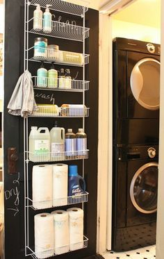 Laundry room with Home Depot white door rack, Mrs. Meyer's cleaning products and stacked black front-load washer & dryer.