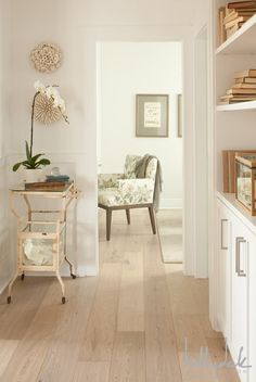 Gorgeous hallway featuring white walls and light wide planked hardwood floors. The hallway includes built-in bookcases and cabinetry adorned with books. In the corner of the hall, stands a vintage metal accent table topped with a white orchid. Coral wall decor hangs over the accent table. Just off of the hall stands a floral chair below a pair of framed prints.