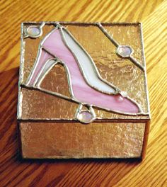 A pink glass shoe on the lid of this dainty keepsake box.