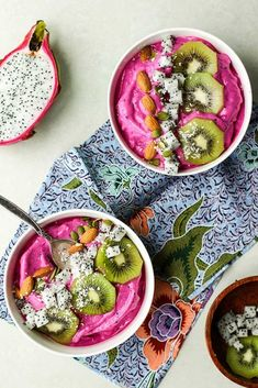 Two pitaya bowls and topped with kiwi, coconut and almonds.