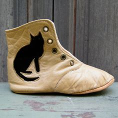 "One child's shoe or half boot. Soft light tan leather with an appliqued black leather cat on both sides. Five, front lacing holes with a tongue, rounded toe, circular vamp, no heel and back seam. C1850 - 1860. ~ Donna Finegan Antiques ( The original ""Robies"")!"