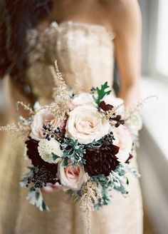 White roses paired with dark flowers and mini berry accents complete this winter wedding bouquet.