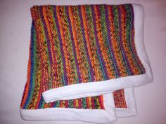 Simple knit blanket for the baby car seat.  Fairisle pattern wool, garter stitch, hemmed with an old white tee.