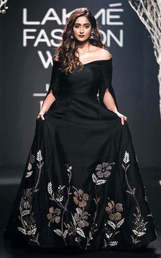 Ileana D'Cruz looked bewitching in a black off-shoulder, full-flared dress with floor-kissing sleeves as she walked the ramp at the LFW 2017 event. (Source: Rediff)