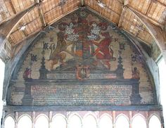 The tympanum displays the achievements of Queen Elizabeth I, depicting the royal arms with a banner on each side. The arms of Anne Boleyn are depicted below, with the date 1587. At the base the Ten Commandments are listed. St Margaret's Church, Norfolk.