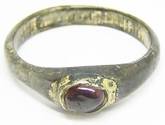 This is a substantial medieval silver-gilt finger ring, dating to the period of the Crusades of the 12th - 13th centuries A.D. The ring is stirrup shaped, set with a natural cabochon garnet gemstone. The ring retains traces of the original mercurial gold gilding inside the band and around the bezel. It is a large and robust example, designed for a man to wear. This ring would have been made during period of the Crusades, either worn by a knight, noble or member of the Church. The ring came…