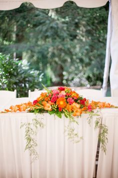 Highlight the wedding party table without blocking the new couple. A low centerpiece frames the two for each married kiss. We used orange Gerbera Daisies, Gladioli, and hot pink Roses, Flowers by A Floral Affair www.afloralaffair.com. Photography by Gabriela Ines www.gabriela-ines.com.
