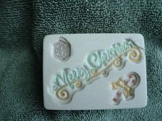 This soap has the words Merry Christmas stamped on it.  It also has a candy cane and a snowflake stamped on the soap.  The soap is painted with