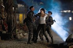 """The second they touch her, Kate snaps into action. Her elbow smashes into the face of the soldier behind her, and easily breaks the grip of the soldier holding her wrist just before breaking his knee with a quick kick. Before he can cry out, she lands a quick left hook on his jaw, and both soldiers are out cold. She smiles at the guys. """"Got the uniforms!"""" She whispers brightly."""