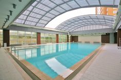 Solarkent / İstanbul Situated in Istanbul this large retracting roof covers a residential shared pool. This motorized 18m wide by 22m long retractable roofing was built for a pool building connected to a large apartment complex. From design to turnkey, this installation took 10 weeks to complete. The 22 meter pool roof allows the pool to be used in any climate allowing all the tenants of the residential complex complete and year round use of their pool.
