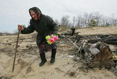 An elderly woman visiting the cemetery of the abandoned village of Orevichi, inside of the 30 kms exclusion zone around the Chernobyl nuclear reactor.