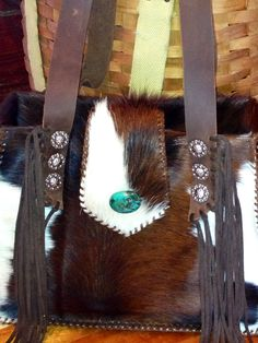 Turquoise stone, suede fringe and lots of room for all of your things. Cowhide purses at gowestdesigns.us.