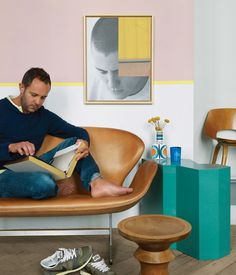 Designer Jean-Christophe Aumas reads on a vintage Swan sofa by Arne Jacobsen. The teal side table is from a Berlin flea market; the walnut stool by Charles and Ray Eames is from an antique store in Brussels; Aumas himself made the art on the wall. Photo by: Christian Schaulin