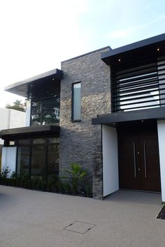 The+central+stone+brick+portion+bisects+the+structure,+flanked+by+expanses+of+glass+that+afford+spectacular+views+from+within+the+home.+A+slim+garden+hugs+the+low+exterior+wall. wall Beautifully Contemporary Nairn Road Project By David James Architects Design Exterior, Modern Exterior House Designs, Dream House Exterior, Modern House Design, Wall Exterior, Exterior Tiles, Exterior Houses, Cottage Exterior, Stone Cladding Exterior