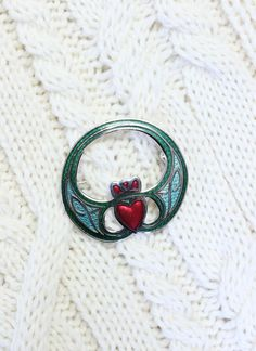 Claddagh Brooch: The Claddagh heart symbol on this charming brooch is highlighted in red with simple Celtic designs complementing either side.The Claddagh's distinctive design features two hands clasping a heart, and usually surmounted by a crown. The elements of this symbol are often said to correspond to the qualities of love (the heart), friendship (the hands), and loyalty (the crown). #claddagh #brooch #jewelry #jewellery #scarfring #pin #irish #celtic Irish Celtic, Celtic Knot, Claddagh Symbol, Scarf Rings, Celtic Wedding Rings, Irish Jewelry, Irish Traditions, Irish Wedding, Celtic Designs