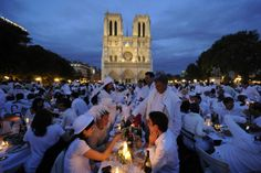 People attend the White Dinner event in front of the Notre Dame Cathedral in Paris, France. Participants attend the dinner, which takes place at a different place in Paris every year, are required to be dressed in white, bring their own food, drink and cutlery to the event. (Reuters)