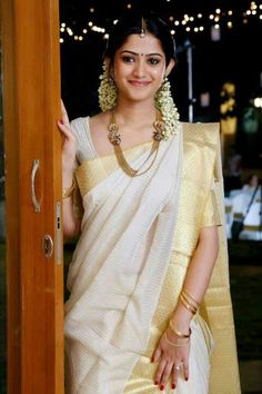 Keralese Sari and simple adornments with gold and jasmine. Traditionally, this sari was worn in two pieces (see my Antariya page for examples). With most girls only knowing one method of wearing the sari, this is the modern style, a modestly draped nivi sari, the only style of draping known by recent generations.