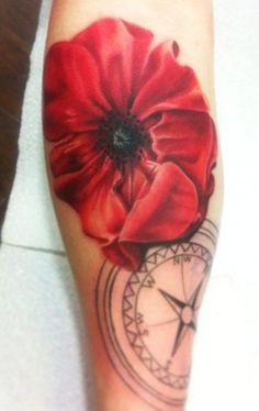 Tattoo of a red poppy and compass.