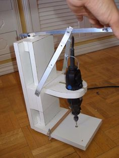 Mini Drill Press by Oscar de los Santos -- Homemade mini drill press constructed from particle board, aluminum flat bar and tubing,  springs, bolts, nuts, and a rotary tool. http://www.homemadetools.net/homemade-mini-drill-press-5