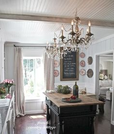 Love the variance of this kitchen with elegant chandeliers, beaded board ceilings, lighter color pallet with the darker contrasting island.