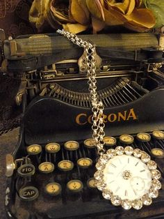 Vintage typewriter draped with a rhinestone watch. Love it!