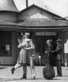 Giovane donna solleva i piedi mentre bacia e abbraccia un soldato statunitense alla stazione. Connecticut, 1945. Harold M. Lambert.