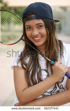 Asian girl smile and hold badminton racket - stock photo