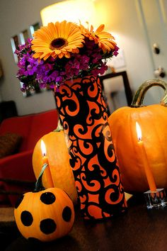 Halloween Spooky Swirl Vase DIY  What you need:   – tall cylinder vase   – orange 12x12 cardstock   – black diecut swirl cardstock (I purchased mine at Joann)   – Aleene's Tacky Spray   – paper cutter   – ruler   – double-sided tape   What you do:   1. Spray the back of your diecut cardstock and place on top of orange cardstock.   2. Measure the height of your cylinder vase. Cut paper to that height using paper cutter.   3. Wrap around cylinder vase and secure in place with double-sided tape.