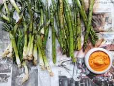 Chef José Andrés likes to serve these calçots, here served with asparagus, in the traditional manner: on a newspaper. The newspaper traps in steam from the cooling calçots, making them more tender and soaking up any excess oil. These tender Spanish green onions, always served with Romesco sauce, are a classic springtime treat.