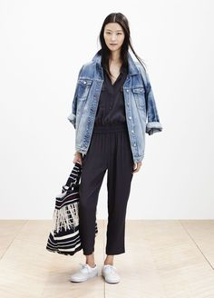 Shop this look on Lookastic:  http://lookastic.com/women/looks/blue-denim-jacket-black-jumpsuit-black-and-white-tote-bag-white-plimsolls/8271  — Blue Denim Jacket  — Black Jumpsuit  — Black and White Horizontal Striped Canvas Tote Bag  — White Plimsolls