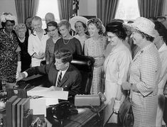 1963: Women celebrate with John F. Kennedy as he signs the Equal Pay Act. | 13 Photos Of Women Fighting For Equal Pay Throughout History