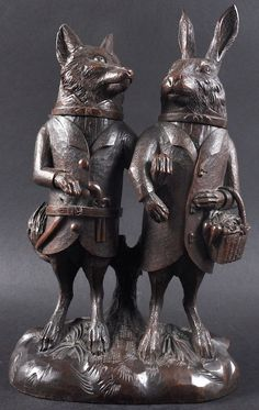 A VERY RARE 19TH CENTURY BLACK FOREST CARVED WOOD GROUP OF A STANDING FOX AND A RABBIT, each standing side by side, arm in arm, the heads hinged and opening to reveal a compartment for spice etc. 16ins high.