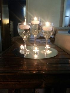Wine glasses for centerpieces with floating candles, but instead of the tealights on the mirror with them maybe have votive candles in clear holders.