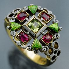 NEO-RENAISSANCE  Revivalist Ring   Gold Enamel Demantoid Garnet Ruby  H: 1.6 cm (0.63 in)  W: 2.2 cm (0.87 in)   British, c.1870  Ring Case  Unmarked, in the style of Giuliano.  Literature: cf. Castellani & Giuliano, Revivalist Jewellers of the Nineteenth Century,   Geoffrey C. Munn, 1984, p. 174    Ref: 4331