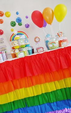 Rainbow Party decor - colourful ruffles, balloons and pompoms. Cute, but the ruffles would be a bit too much work for me.