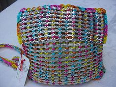 https://flic.kr/p/4fwqMc | Backpack | OMG, I love this one!!! The color is so awesome...  Roomy and shiny. I used almost 900 clean post-consumer aluminum pop tops or pull tabs from soda and beer cans.  This one is crocheted with very fine (#2) Omega nylon cord for the body of the bag and thicker (#18) for everything else. Nylon cord is used for macrame and fishing nets, so it's extremely strong and durable. Also, pretty resistant to soiling and staining.  The lining is 100% bright yellow…