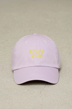 """A cotton woven dad cap featuring an embroidered """"Never Again"""" graphic on the front and an adjustable back."""