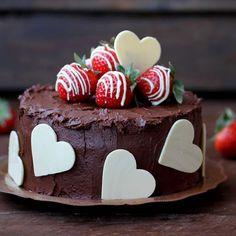 Pastel de chocolate y fresas con corazones de chocolate blanco