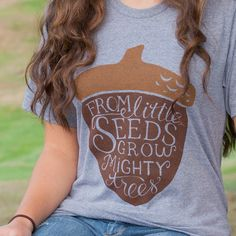 This T-shirt features the quote From Little Seeds Grow Mighty Trees, hand lettered into an adorable acorn silhouette. Once just a pencil sketch, now a wearable design. Celebrate your own journey with