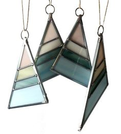 Handcrafted in milky opaque glass, these stained glass triangles can be hung on a holiday tree or year round in a window. Each small stripe is individually cut and joined using the traditional lead soldering techniques and enclosed in a zinc frame for sturdiness. The triangles are all one of a kind, and the one you receive will be crafted with panels of colorful marbled glass in blush, cream, emerald and sky, which will change in hue when illuminated.
