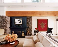 Exposed beam, stone and black surround create rustic contrast in a contemporary living room in California