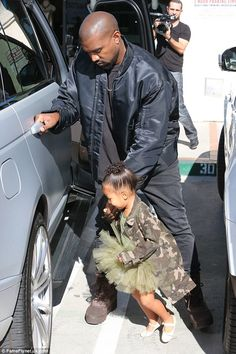 Almost there: Kanye carefully led North to the gun-metal grey SUV