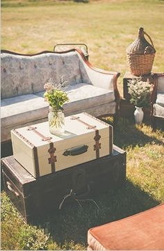 outdoor farm wedding idea: make seating areas in the field with sofas and vintage luggage stacked as tables.