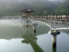love the dichotomy of the traditional architecture on top of the sterile, modern concrete columns. Moon Bridge, China