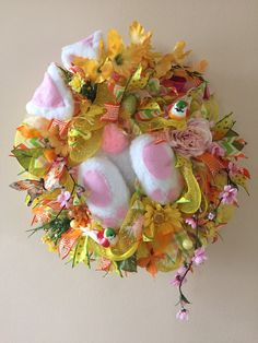 Spring Deco Mesh Wreath. Curious Bunny.  Base is yellow deco mesh. 4 kinds ribbon strips. Added different kinds of flowers, small watering can and propeller, cute bunny ears and butt, easter egg, birds and butterflies and feathers.  More you can find at https://www.facebook.com/Moje-vence-995508700482994/
