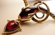 A Mid 19th Century Snake Necklace This superb Victorian era gold necklace is designed as a finely carved almandine garnet snake head holding an almandine g